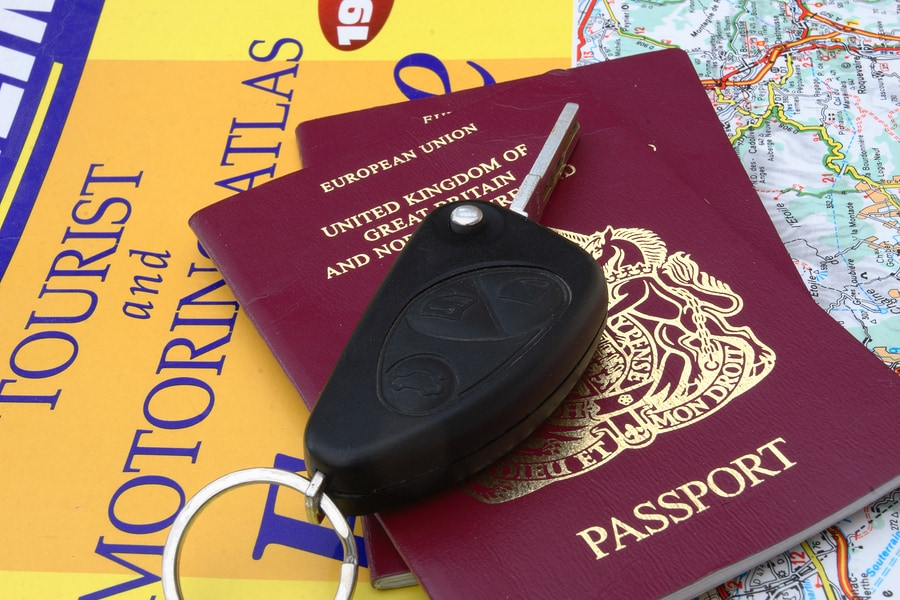 car key travel documents and map for driving abroad