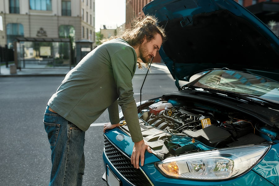 man inspecting a car after a stall