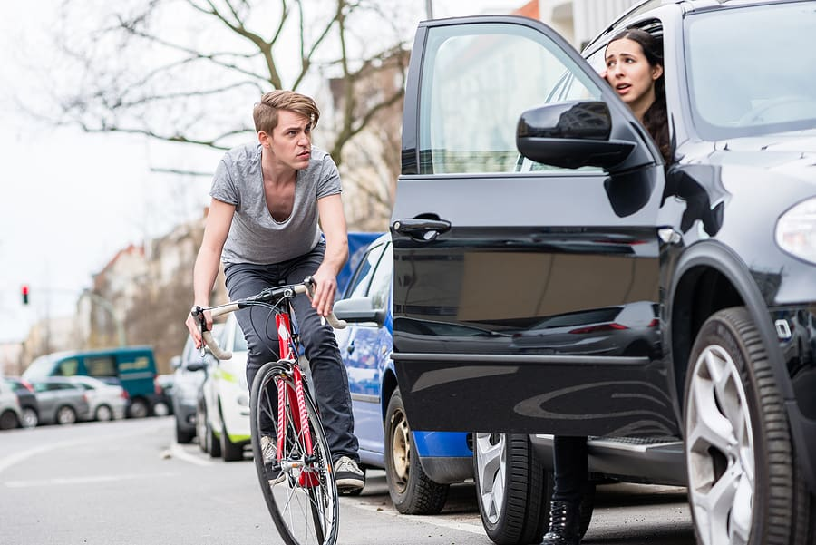 opening a car door in front of a cyclist